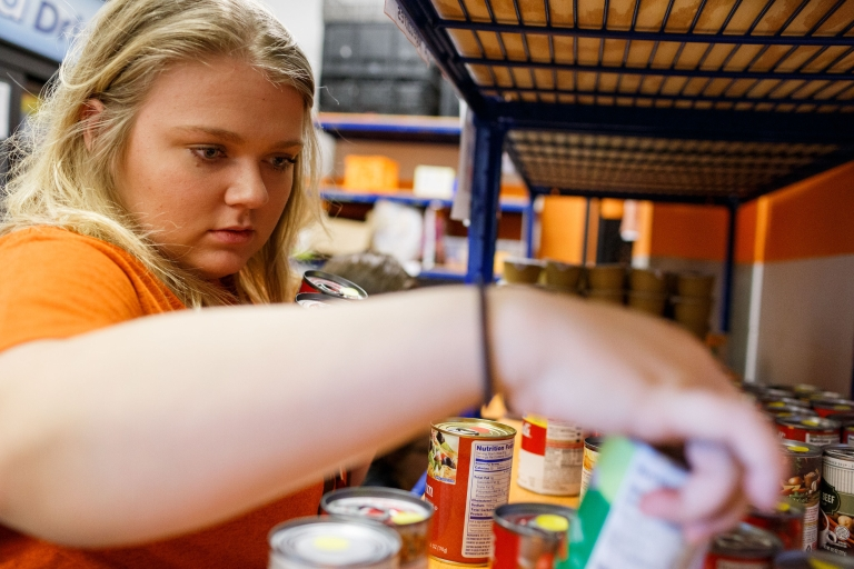A student helps stock food at Paws Pantry on the IUPUI campus.